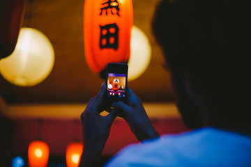 Young man making a picture of Japanese red lantern at night with mobile phone