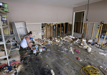 Sheryl Howard tries to salvage cans of paint in her flood damaged garage at the South Point subdivision in Denham Springs