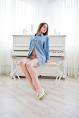 Young tender sexy brunette girl in underwear and denim shirt posed against piano. Studio fashion portrait of model.