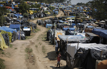 """A father and son look on at """"New Palestine"""" camp, which houses an estimated 8,000 families of Brazil's Roofless Workers Movement in Sao Paulo"""