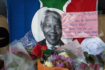 A South African flag with the image of Nelson Mandela on it hangs on a fence along with a note and bouquets of flowers in front of the Town Hall in Cape Town