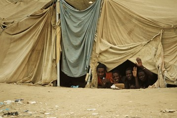 Ethiopian migrants look from their makeshift shelter near a transit center where they wait for repatriation in the western Yemeni town of Haradh