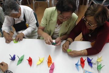 Rosa Arashiro and Hiruko Omura make origami cranes to support Japan's earthquake and tsunami victims at the Peruvian Japanese Cultural Center in Lima