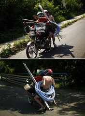 Two men carrying tools and plastic tubes ride a motorbike outside Donetsk