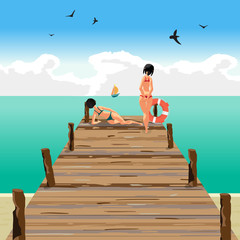 Two young women on a wooden pier on the beach looking at a sail