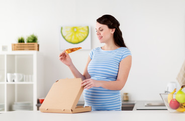 happy pregnant woman eating pizza at home kitchen