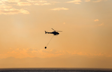 The helicopter collects water from the sea to extinguish a fire