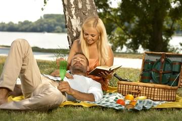 Casual man sleeping at picnic in lap of girlfriend
