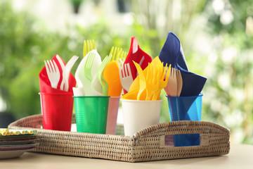 Plastic ware in wicker tray outdoors