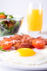 Breakfast with fried eggs and bacon with fresh salad and toast on the table.