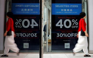 Woman walks outside a fashion boutique in a shopping district in Tokyo