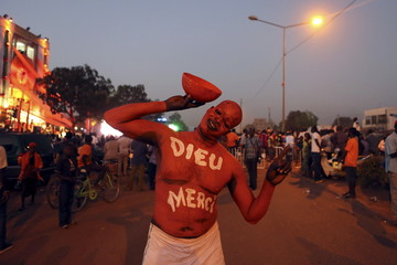 """A supporter of Burkina Faso's President-elect Roch Marc Kabore wearing body paint that reads """"Thank God"""" poses for a picture outside Kabore's campaign headquarters in Ouagadougou"""