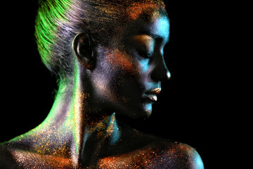 Portrait of beautiful young woman with dark paint and sparkles on her body, dark background