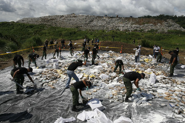 Anti-narcotics police officers destroy confiscated drugs before incinerating the drugs in Panama City
