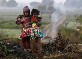 Girls stand near smoke from twigs which were set on fire by their parents to warm themselves at a vegetable field in New Delhi