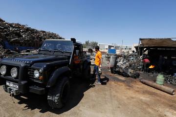 Jordanian graphic designer Abdelrahman Asfour, who turns car parts into furniture, loads car parts onto his truck at junkyard in Amman