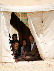 Displaced Iraqi people, who fled from Falluja because of Islamic State violence, sit inside a tent at a refugee camp in Ameriyat Falluja
