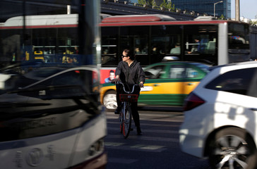 A woman riding a Mobike's shared bike is pictured at a crossing in Beijing's central business area
