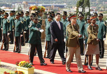 China's President Xi Jinping inspects the honour guard during a working visit to South Africa