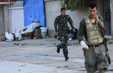 A personnel of pro-government Libyan forces, who are backed by locals, runs during clashes in Benghazi