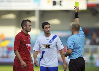 Referee Marciniak shows a yellow card to Sandor of Videoton and Melli of Gent during their Europa League third qualifying round second leg soccer match in Ghent