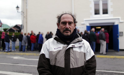 An Argentine veteran of the Falklands War, Gustavo Jimenez, poses for a picture as people line up to cast their vote at the Town Hall polling station in Stanley
