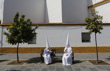 Penitents of San Gonzalo brotherhood sit as they wait to take part in a Holy Week procession in the Andalusian capital of Seville, southern Spain
