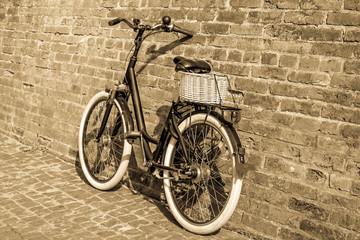 Photo sur Aluminium Black retro vintage bicycle with old brick wall.