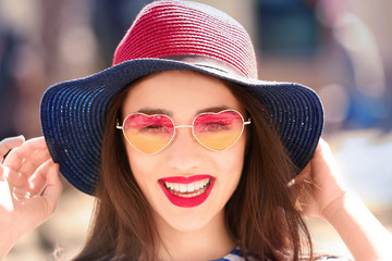 Beautiful young woman with sunglasses and hat outdoors