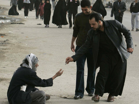 A man gives money to a beggar on a street in Basra