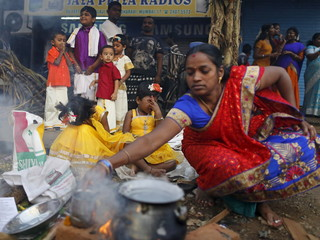 Girls react to smoke as their mother prepares ritual rice dish to offer to the Hindu Sun God as they attend Pongal celebrations at a slum in Mumbai