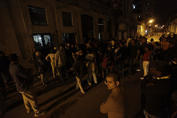 Pro-government supporters stand in the street outside home of the leader of The Ladies in White in Havana