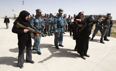 New female recruit of the ANP stands guard as fellow recruits practice arrest techniques during a training session in a police base south of Herat
