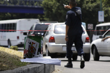 A policeman walks next to a gift bag and a message at a crime scene in Cuernavaca