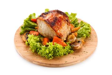 Roast ham with vegetables on wooden desk
