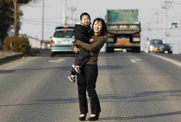 Yuko Sugimoto and her son Raito stand at the same place she stood in March 13, 2011