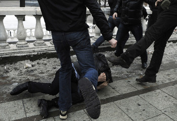A group of right-wing protesters beats up a passer-by they consider to be from Russia's North Caucasus region during a rally in central Moscow