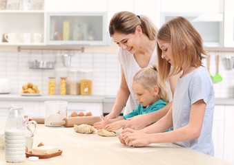 Young woman and her daughters cooking in kitchen