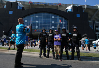 Football fans take a picture with riot police, outside a stadium in Charlotte