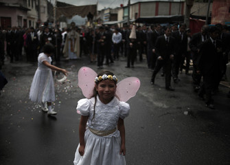 "A girl wearing butterfly wings poses during the ""Corpus Christi"" procession in the streets of Guatemala City"