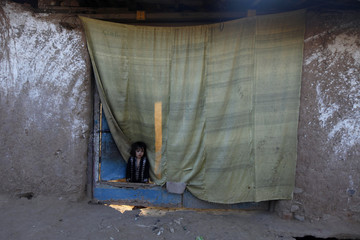 A girl looks out of her house at a slum on the outskirts of Islamabad