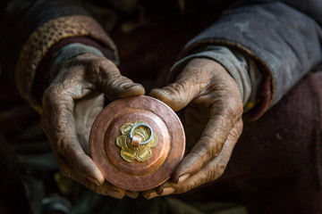 An old craftsman is holding in his hand a cup, traditional Tibetan copper handicraft product in his workshop in Chilling village in the Indian Himalaya. Chilling, Ladakh, India