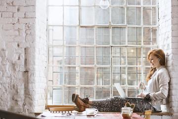 Woman sitting on windowsill with notebook