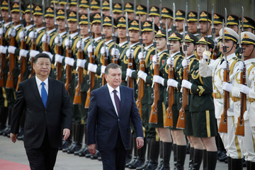 Uzbekistan's President Shavkat Mirziyoyev and China's President Xi Jinping inspect honour guards during a welcoming ceremony in Beijing