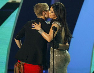 Justin Bieber hugs presenter Kim Kardashian after he won best male video at the 2011 MTV Video Music Awards in Los Angeles