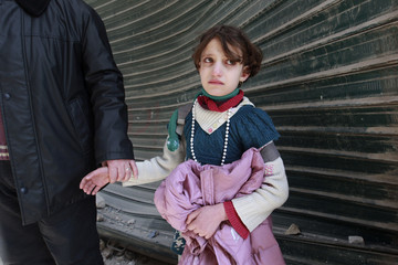 A girl who returned from school cries upon seeing her house destroyed after a jet missile hit the al-Myassar neighbourhood of Aleppo