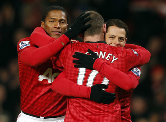 Manchester United's Rooney celebrates his goal against West Ham United with Valencia and Hernandez during their FA Cup third round replay soccer match in Manchester