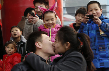 Children look at a couple kissing at a kissing contest for celebrating the Valentine Day at the Happy Valley amusement park in Beijing