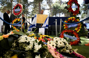 A man holds picture of dove with olive branch together with Israeli flags near wreath-covered grave of former Israeli President Peres, after burial ceremony at funeral in Mount Herzl Cemetery in Jerusalem