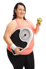Overweight woman holding a weight scale and an apple